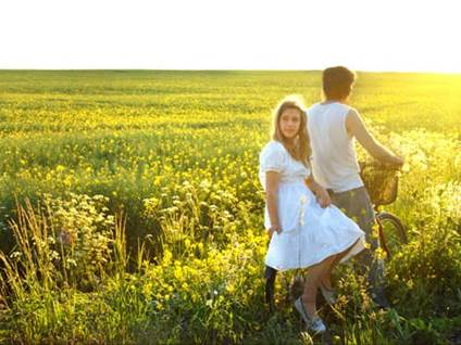 Man and woman on a bicycle in a summer field