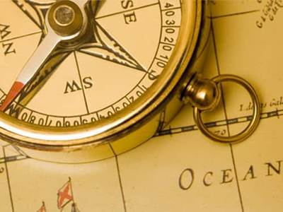 Gold compass on a vintage world map