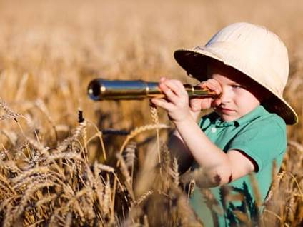 Little boy in a safari hat looking through a telescope