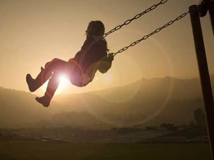 Little girl on a high swing at sunset