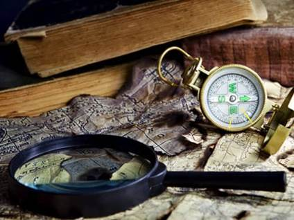 Magnifying glass, compass, world map, and old books