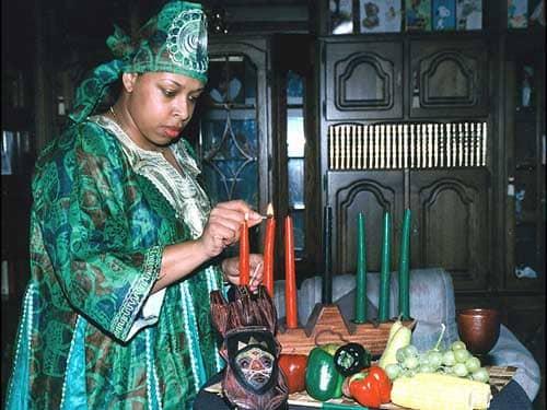 Woman lighting Kwanzaa kinara