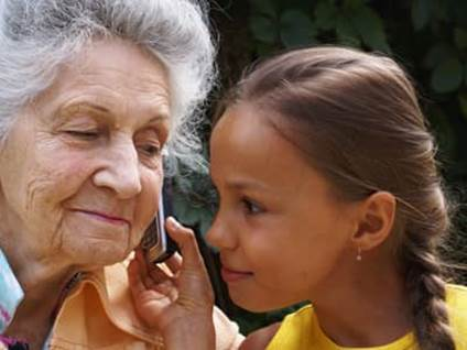 Grandmother and granddaughter listening to a cell phone