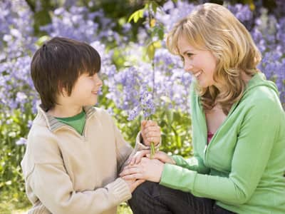 Son handing a flower bouquet to his mother