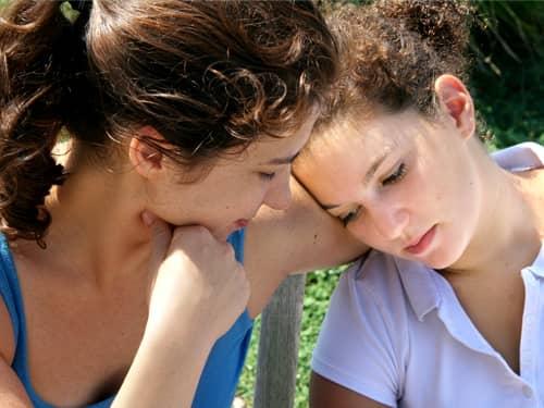 Girl comforting a sad friend