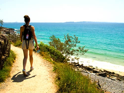 Woman hiker on a path by the beach