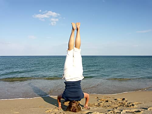 Standing on head by beach