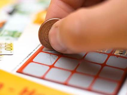 Fingers using a penny to scratch a lotto ticket