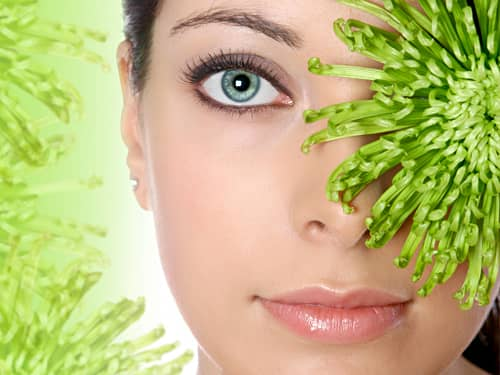 Green-eyed woman hiding behind a flower