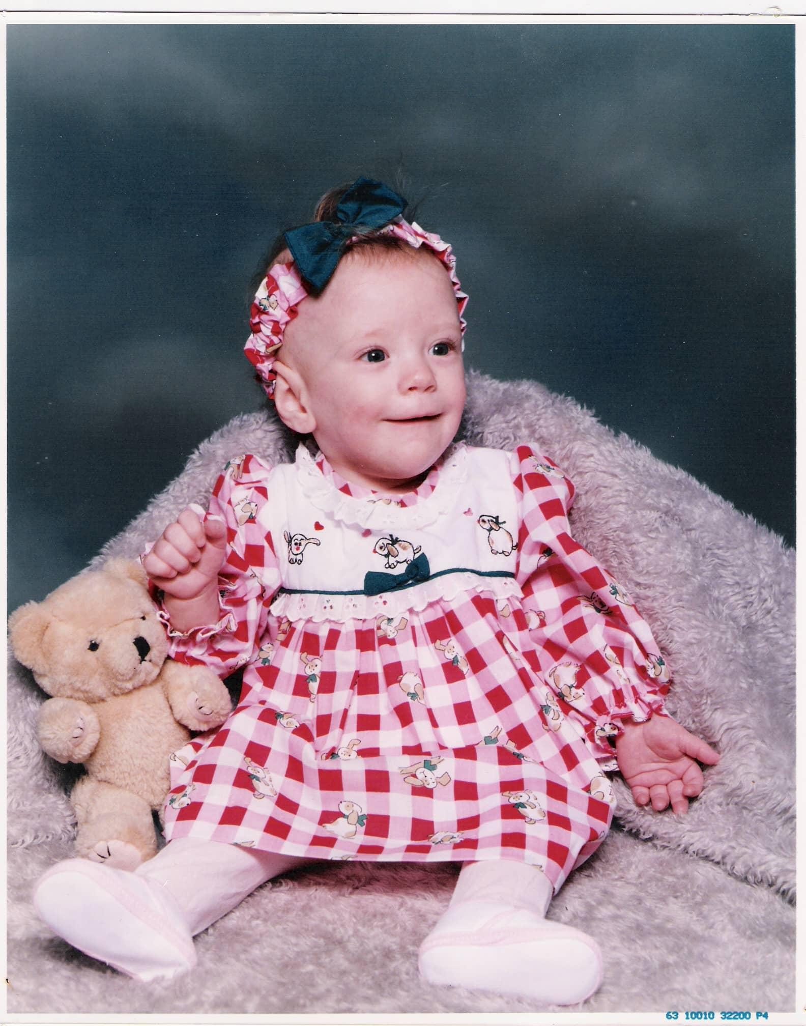 Cute baby girl in a red checker dress