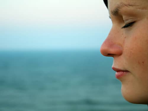 Woman praying and meditating by the ocean