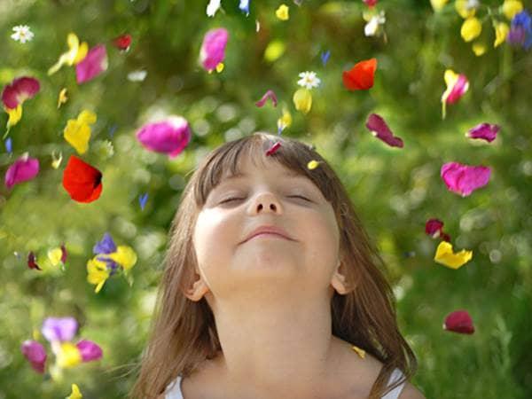 Flower petals falling around a little girl