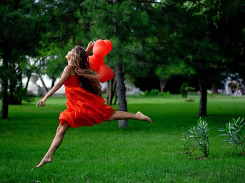 Woman leaping in red dress with red heart balloons