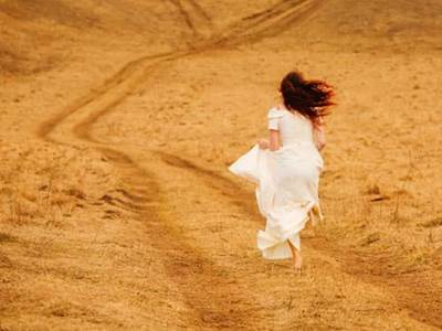 Woman in white dress running on dirt road