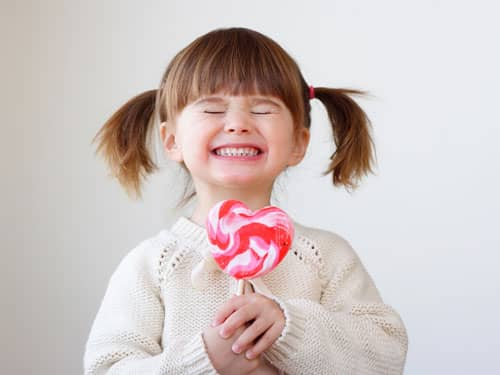 Little girl holding pink lollipop
