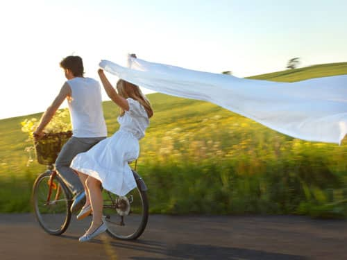 Man and woman riding a bicycle at sunset