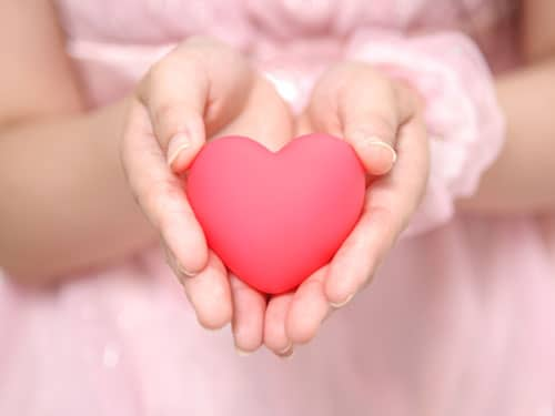 Little girl in a pink dress holding a pink heart