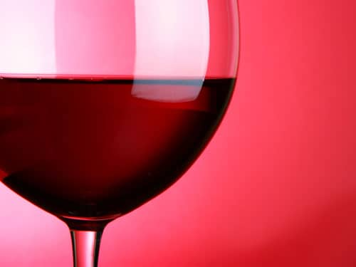 Glass half-filled with red wine