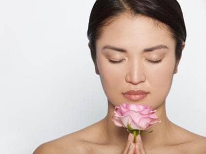 Asian woman praying pink rose