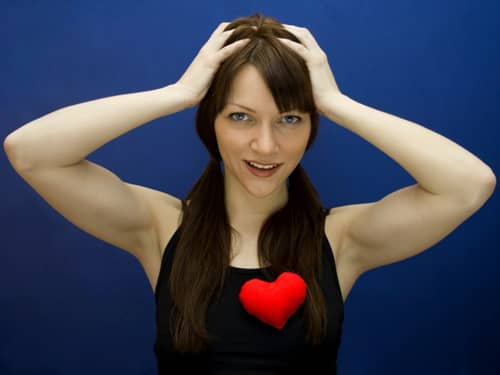 Woman holding head and wearing heart on shirt