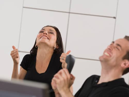 Man and woman thumbs up and excited at work