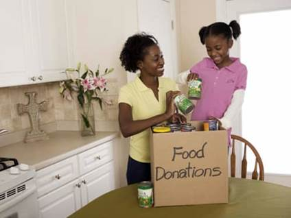 Mother and daughter filling food donation box