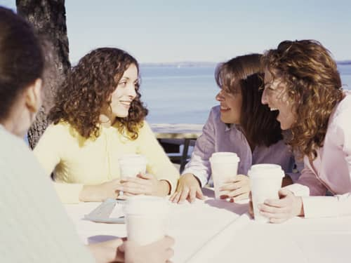 Group of women talk over coffee