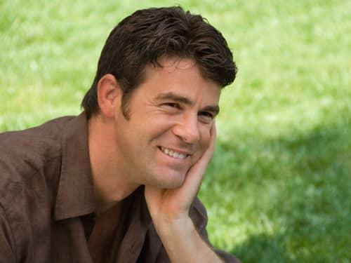 Man smiling, one hand on cheek