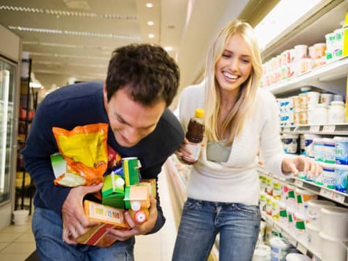 Man and woman holding items at grocery store