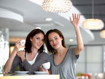 Young women drinking coffee and waving