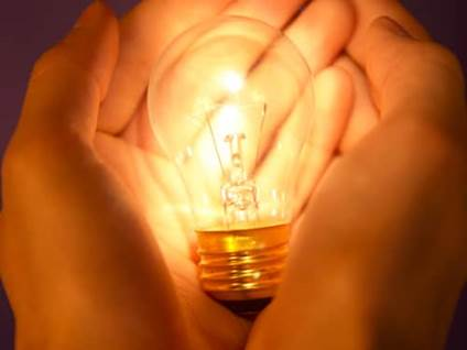 Two hands cupping lit lightbulb