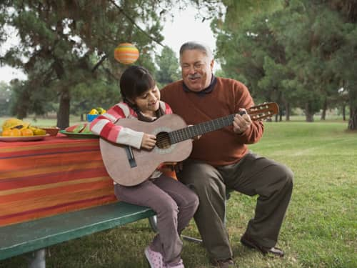 Older man and young girl playing guitar together
