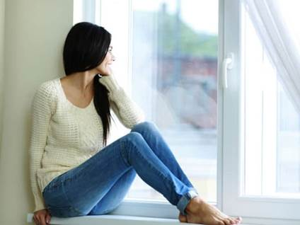 Young Woman Sitting on a window ledge