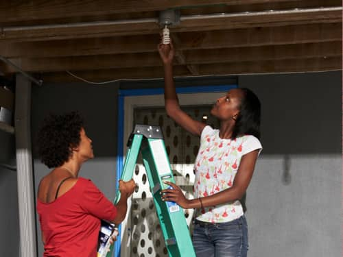 Two women painting ceiling