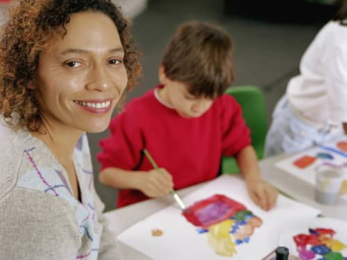 woman smiling and child painting