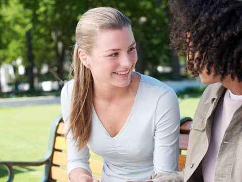 women talking on park bench