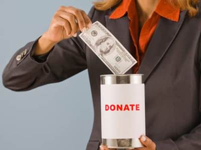 woman placing dollar into donation can
