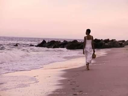 Woman in white dress walking on a beach