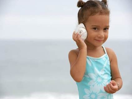 Little girl listening to a seashell at the beach