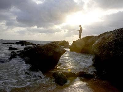 Man fishing near the ocean