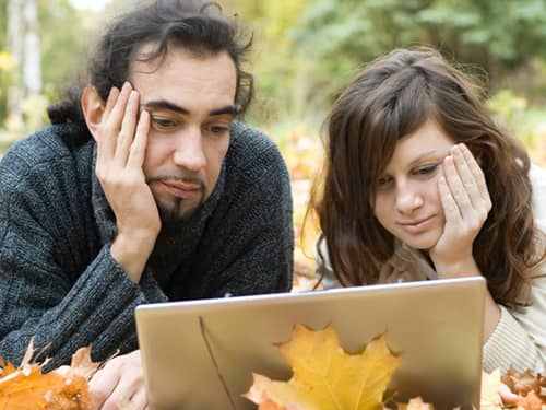 Young couple on laptop in the park