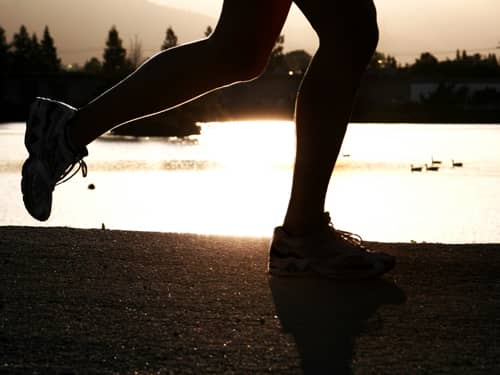 Woman's legs running on the beach.
