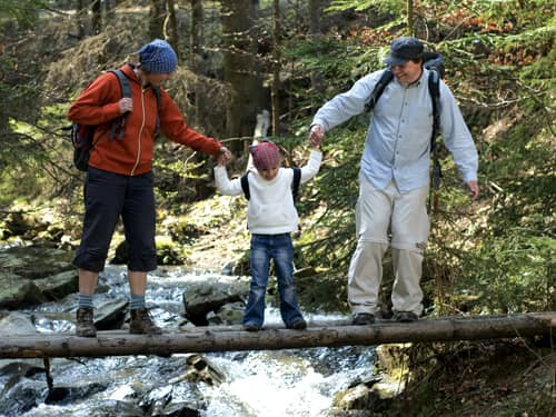 Parents crossing river, holding child between them