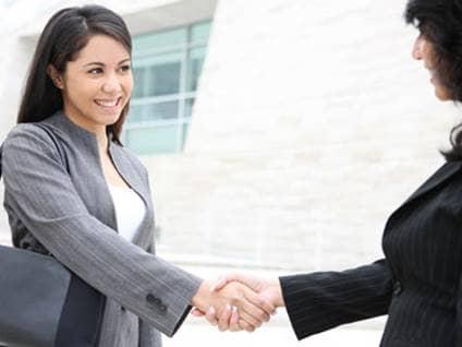 Young women shaking hands
