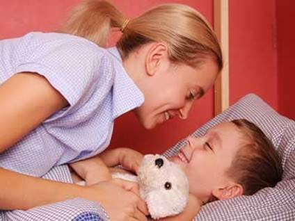 Mother tucking son into bed
