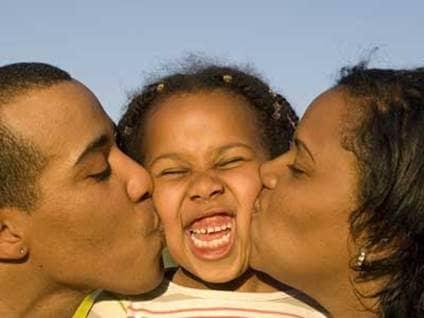 African-American parents kissing daughter