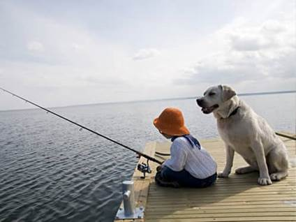Little girl fishing, with a yellow labrador retriever at her side