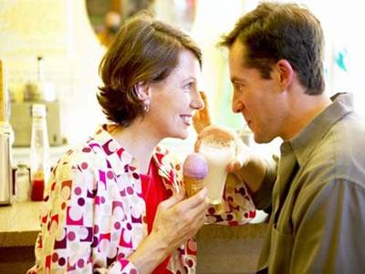 Man drinking milkshake Woman eating ice cream cone on a date