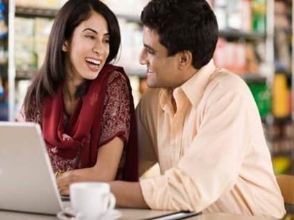 Man and woman looking at a laptop on a date