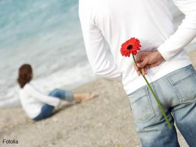 Man approaching woman with flower behind his back